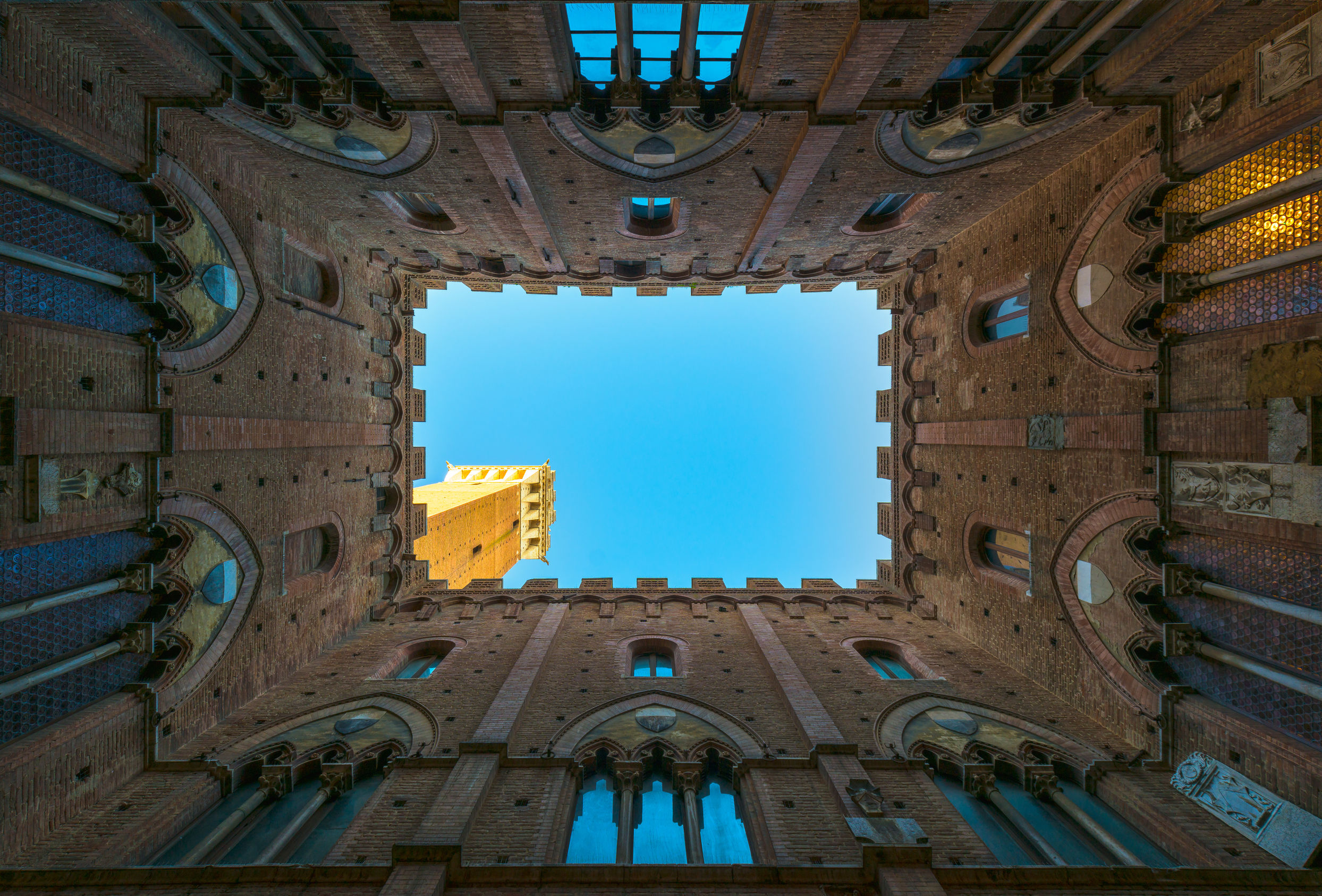 Siena landmark photo. Cortile del Podesta and Mangia tower. Tusc